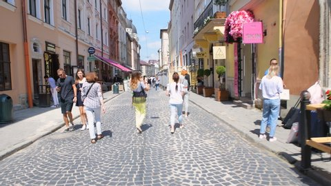 Lviv, Ukraine - August 1, 2018: Pov point of view walking on Katedralna square street in Lviv, Ukraine on sunny summer, stores, shops young people shopping