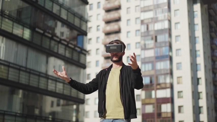 Tracking slow motion shot of young man in vr glasses standing outdoors in city street and exploring virtual reality | Shutterstock HD Video #1034625386