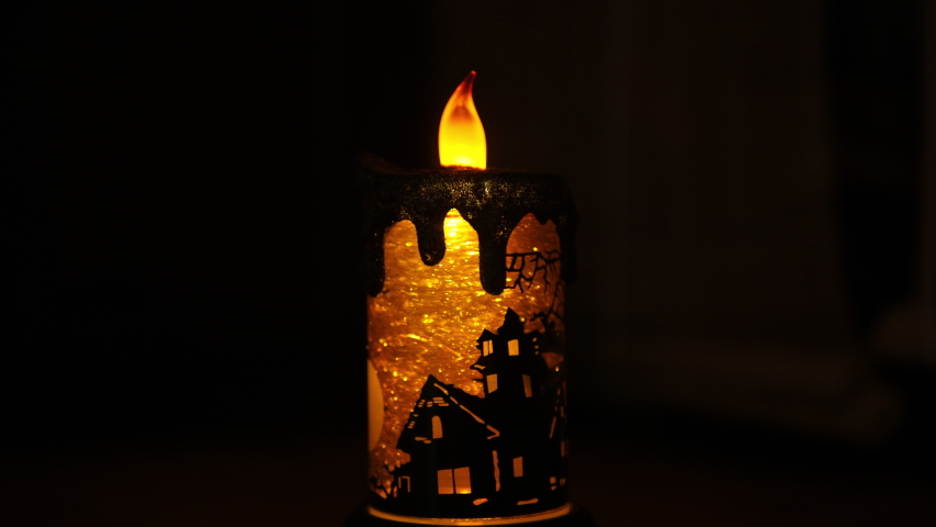 Halloween Candle Lighted Lamp, Spinning Water Glittering Tornado for Celebration Parties. Witch, bat flying in cemetery | Shutterstock HD Video #1034633726