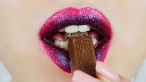 Extreme close-up of lips of a young woman. Woman eating a slice of dark chocolate with filling. Women's morning makeup