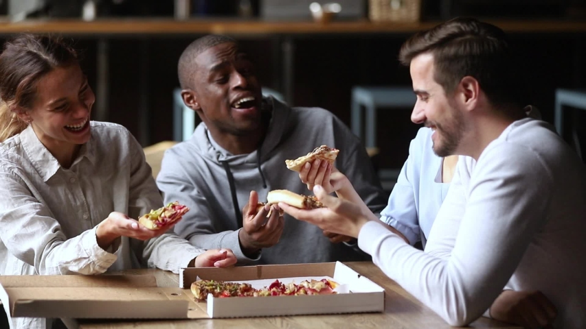 Multiracial friends sitting at table in cafe drink coffee or tea spending free time weekend together chatting laughing share eating pizza gathered in pizzeria public place, telling jokes anecdotes hav