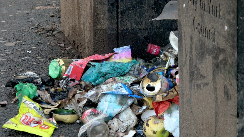 York / United Kingdom (UK) - 02 23 2019: Zoom out from Loose Litter piled up next to a City of York Council refuse bin showing the garbage spilling onto the footpath. York, North Yorkshire. | Shutterstock HD Video #1034792966