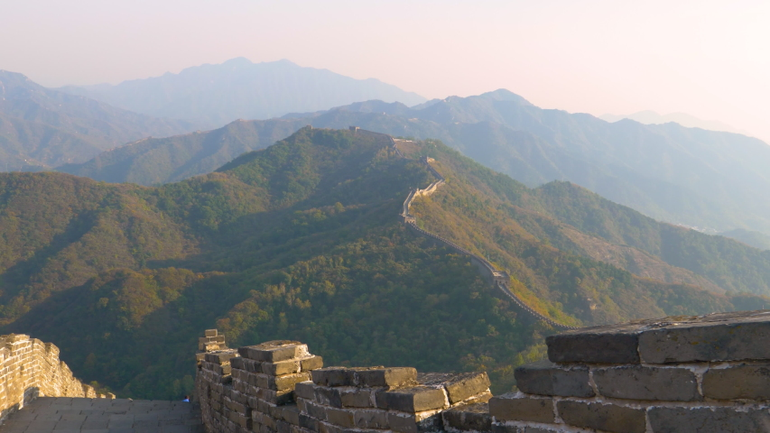 Breathtaking view of the empty cobblestone walkway atop the Great Wall running across the vast green mountains of rural China. Golden evening sunshine illuminates Great Wall of China and the forests.