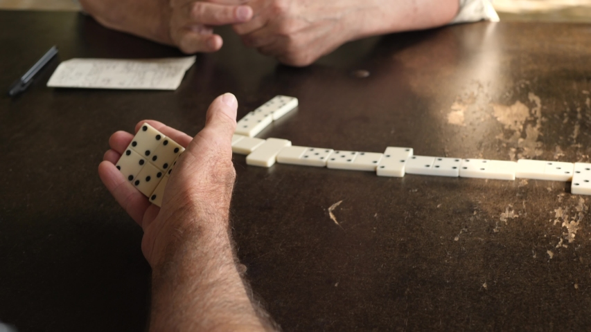Active retired men's hands playing game of domino at table. Leisure, retirement or recreation concept   Shutterstock HD Video #1034867216