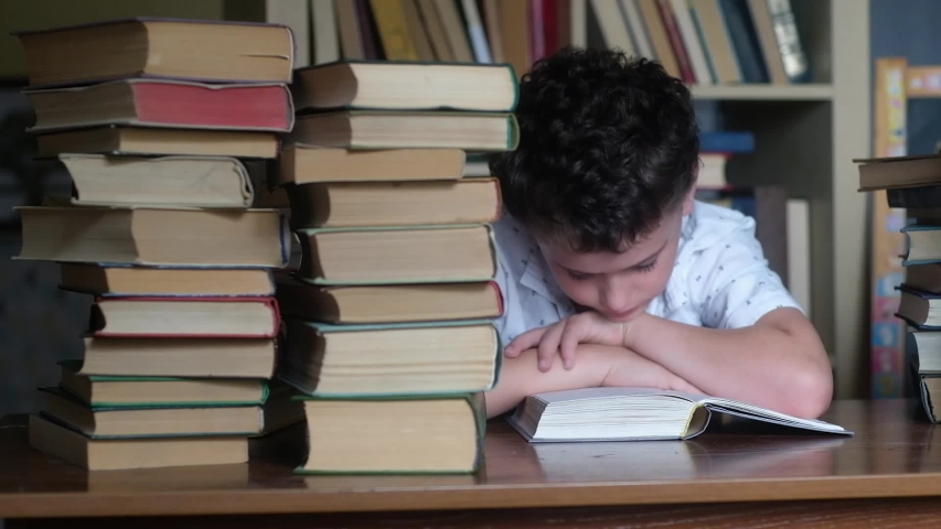 Boy light shirt sits at wooden table and reads thick book. He put his hands on her and rested his chin. Literature stands in columns on table. Panoramic shooting on background of the bookshelf. | Shutterstock HD Video #1034960036