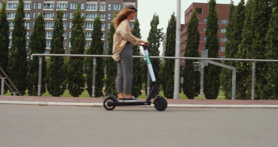 Girl rides an electric scooter or e-scooter roller in hamburg city germany, ecological e mobility in the urban city, 4k Steady Parallel Side Shot, modern transportation | Shutterstock HD Video #1034995676