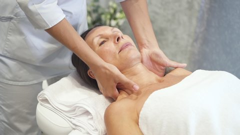 Charming and calm woman with closed eyes spending free time on relaxing procedure. Female lying on massage table enjoying health touch of professional in bright and light spa salon