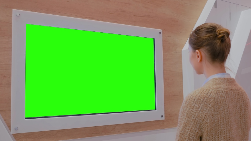 Woman looking at blank digital interactive green display wall at exhibition or museum with futuristic interior. Mock up, future, copyspace, template, chroma key, green screen, technology concept   Shutterstock HD Video #1035027776