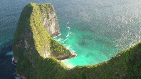 Aerial view of Kelingking beach, Nusa Penida, Indonesia with danger hiking trail on the top of mountain leading to amazing sandy beach with azure clear sea water. 4k