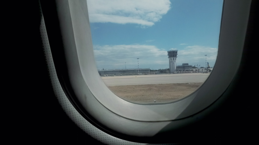 First-person POV: looking outside the window of an airplane moving on the runway, preparing for the takeoff.  | Shutterstock HD Video #1035077486