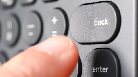 Closeup of finger pressing backspace button on the black computer keyboard. Technology