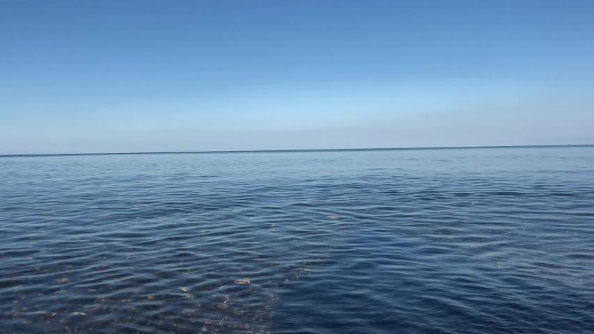 The sea off the coast creates a blue background. The sea merges with the sky. The calm, clear water of the Black Sea off the coast of Georgia, in Batumi. #1035134336
