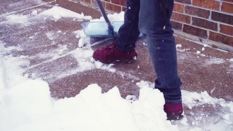 Slow motion. Young man shoveling snow from driveway.