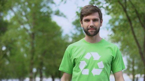 Young environmental activist pointing at recycling symbol t-shirt, segregation