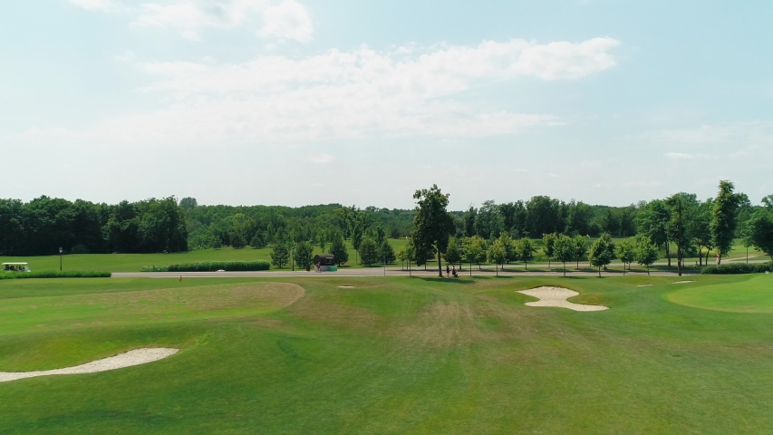 Aerial view of a green golf course with beautiful trees and forest, blue sky with clouds on sunny day in the summer time. 4K drone footage.   Shutterstock HD Video #1035175856