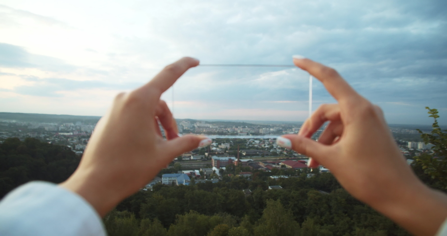 Close-up young woman holding smartphone mock up in both hands scrolling on transparent screen outdoors. Female hands with virtual nobile phone against urban landscape. | Shutterstock HD Video #1035206126