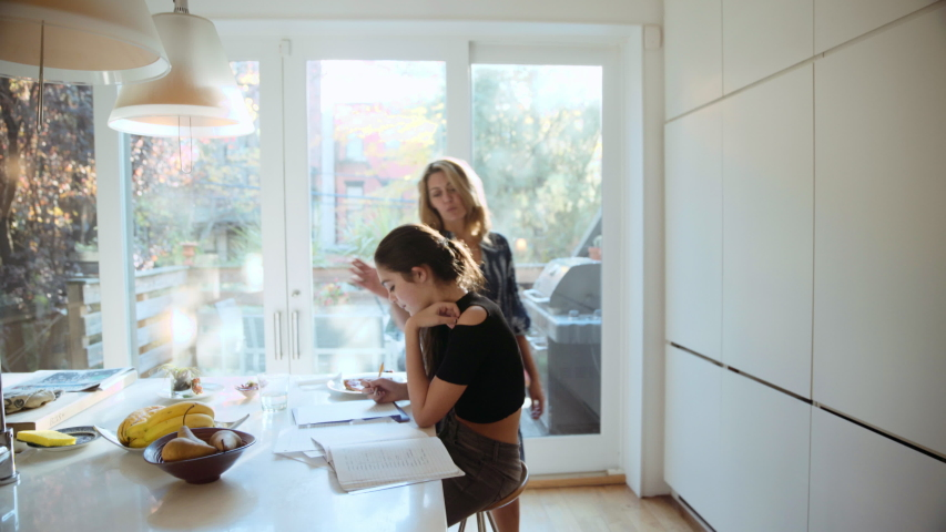 Caucasian mother checking daughter doing homework in kitchen #1035219836