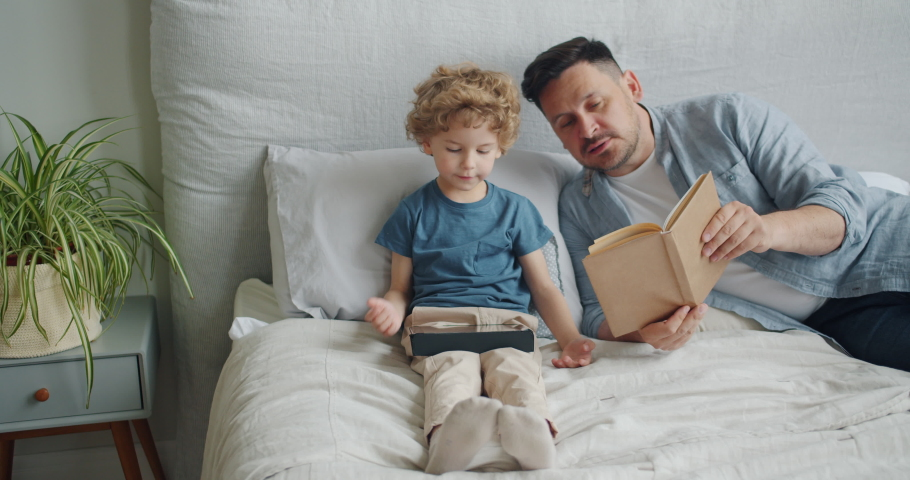 Loving father middle-aged man is reading book to cute child while kid is using tablet touching screen in bed in apartment. Family, literature and gadgets concept. | Shutterstock HD Video #1035238286