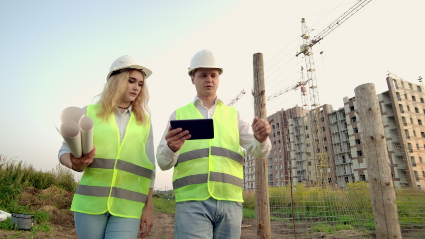 Adult engineer man and architect woman uses a tablet in operation. Writes a message or checks a drawing. Against background is building. | Shutterstock HD Video #1035355316