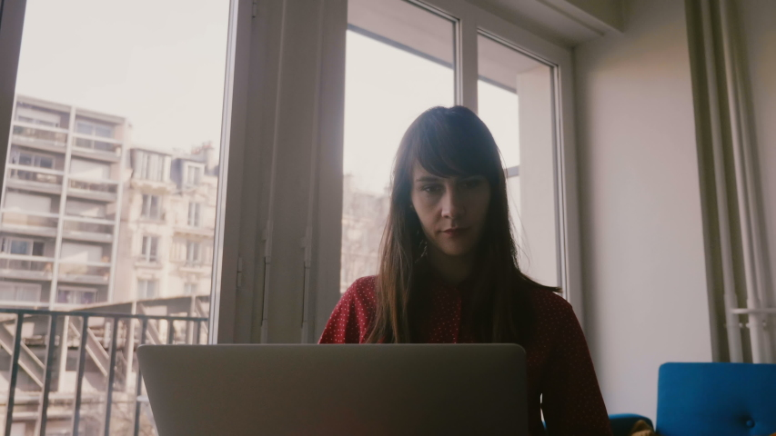 Beautiful focused young businesswoman using laptop and smartphone near apartment window on business trip in Paris.   Shutterstock HD Video #1035394226
