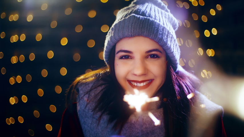 Cute girl with sparkling stick smiling into the camera. Portrait sliding shot of young woman in focus wearing winter clothes and surrounded by decorative lights. | Shutterstock HD Video #1035428396