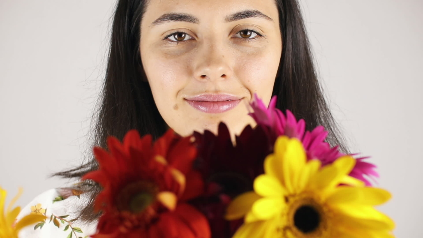 The girl face close up with a bouquet flowers. Portrait of a pretty young woman sniffing a bouquet flowers on grey background | Shutterstock HD Video #1035434036