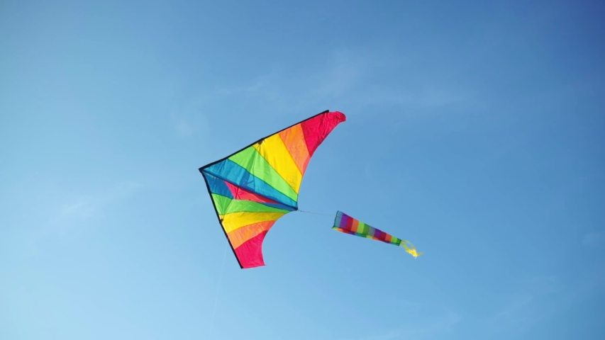 Bright colorful kite flying in blue clear sky on sunny day. Concept of LGBT, freedom and people love concept.   Shutterstock HD Video #1035453026