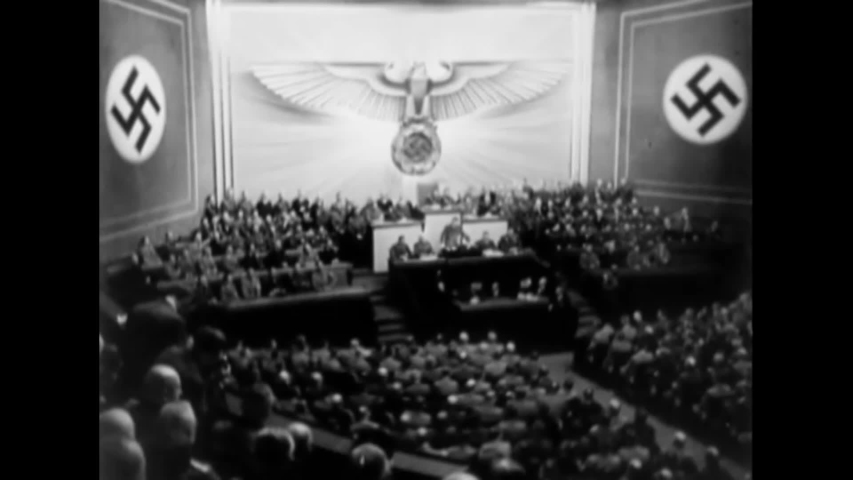 CIRCA 1939 - Hitler makes a speech in a German auditorium. German soldiers blow up buildings in Warsaw.