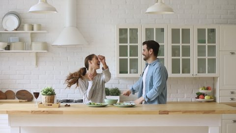 Young happy active family couple dancing laughing together preparing food at home, carefree joyful husband and wife having fun cooking healthy romantic dinner meal listen to music in modern kitchen