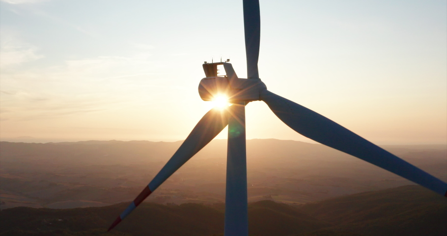 Aerial close up shot of wind mills rotating by the force of the wind and generating renewable energy in a green ecologic way to the planet on a sunset. | Shutterstock HD Video #1035507986