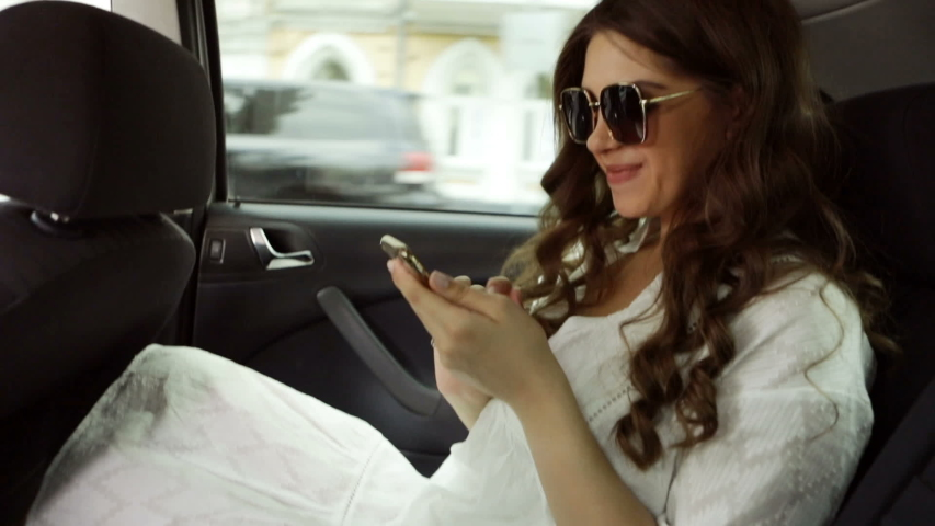 Online shopping on car backseat during car ride. Beautiful woman in the car. Video footage | Shutterstock HD Video #1035510806