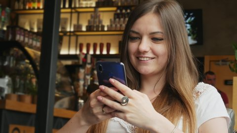 Poltava, Ukraine - june, 2019: Pretty young woman uses a mobile phone and smile in a cafe in close-up