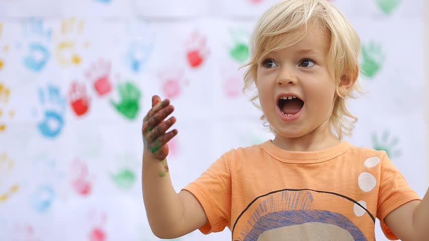 Amazing cute happy child surprising, saying wow and rubbing color paint on his little hands on color handprints background 50fps