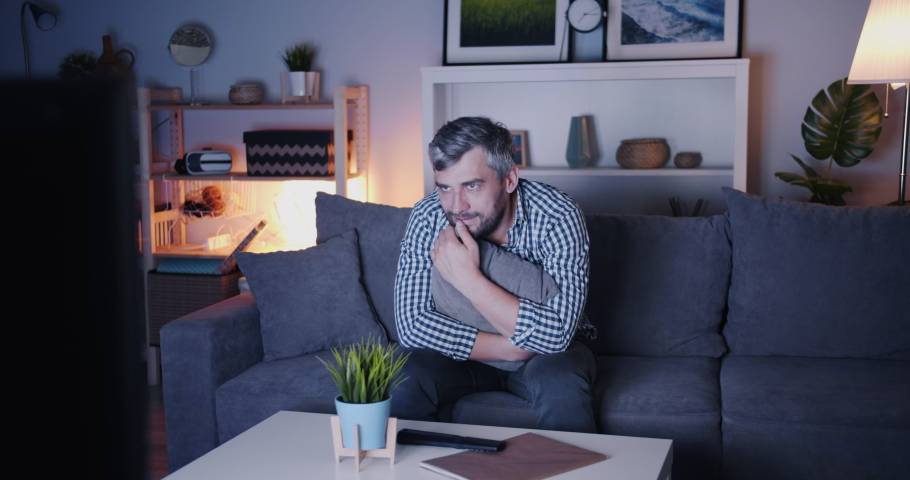 Middle-aged bachelor is watching scary film on TV at night sitting on couch alone holding cushion expressing emotions then using remote control. People and television concept. | Shutterstock HD Video #1035539066