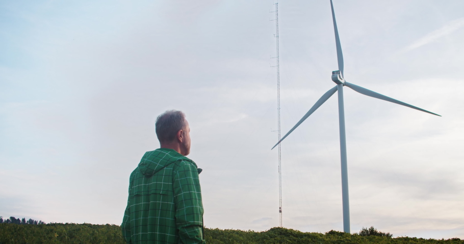 Back view of man in green jacket at windmill power station watching sunset in green harvest fields. Eco-farming. Wind power generators.   Shutterstock HD Video #1035557636