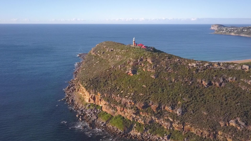 Beautiful Island with a hill top lighthouse with view of two beaches and ocean aerial shot on a clear sunny day. Palm Beach, Sydney Australia. | Shutterstock HD Video #1035579986