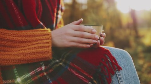 Close up of woman`s hands holding cup of hot tea. Tourist girl wearing tartan scarf enjoys warm drink in autumn park