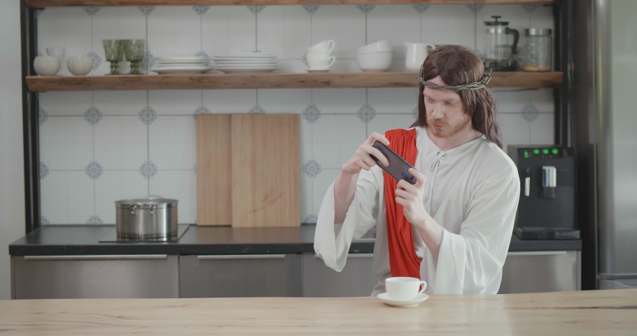 Jesus Christ playing video game on mobile phone and drinking coffee sitting in his kitchen
