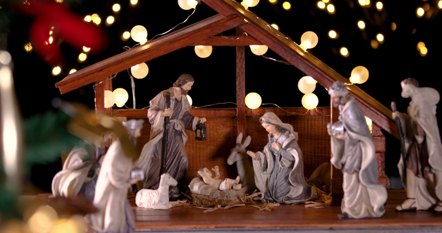 Jesus Christ Nativity scene with atmospheric lights near Christmas tree. Christmas scene. Focus is moving from Christmas tree to manger. Dolly shot 4k | Shutterstock HD Video #1035639986