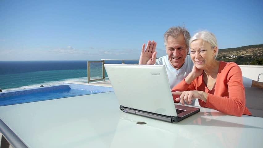 Senior couple waving at webcam