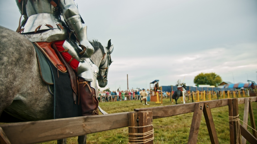 BULGAR, RUSSIA 11-08-2019: Knights battle on the green field - a man waiting for his turn astride a horse #1035657356