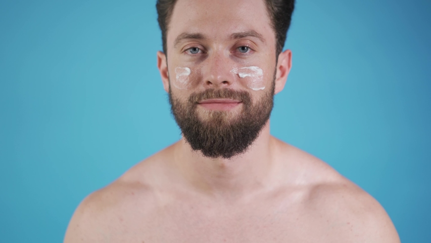 Man applying face cream. Handsome caucasian man. Bearded good looking man. | Shutterstock HD Video #1035670166