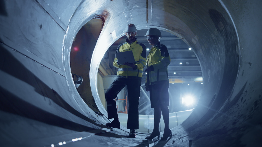 Two Heavy Industry Engineers Walking Inside Pipe, Use Laptop, Have Discussion, Checking Design. Construction of the Oil, Natural Gas and Biofuels Transport Pipeline. Industrial Manufacturing Factory | Shutterstock HD Video #1035703976