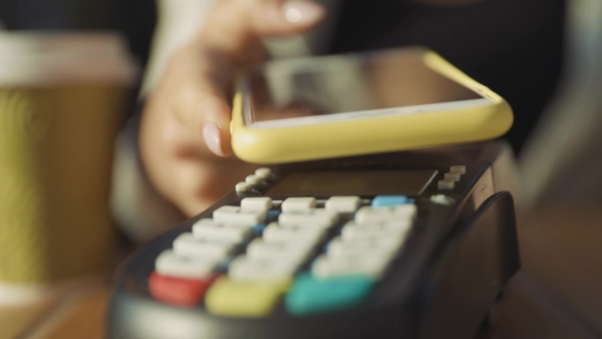 Customer paying for order in the cafe with payment terminal using NFC smartphone technology. Close-up girl applying mobile phone on cash machine. | Shutterstock HD Video #1035891416