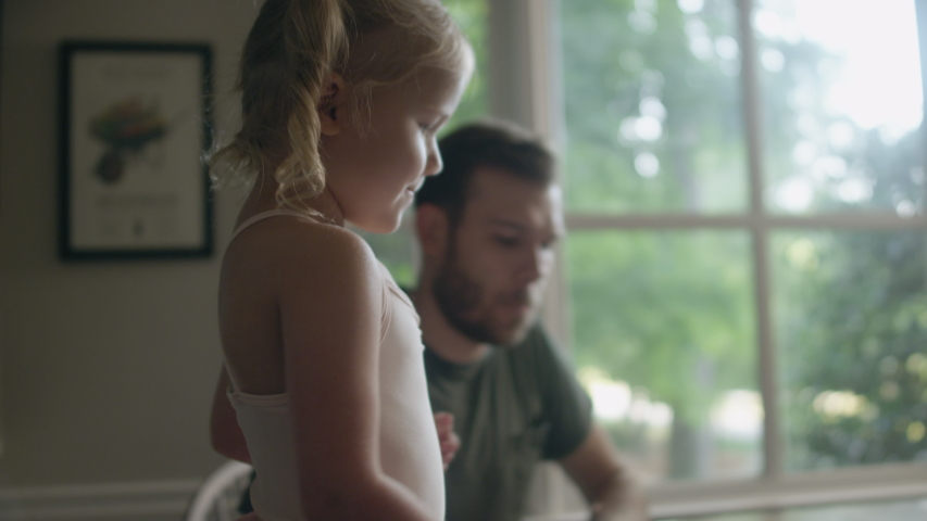 A cute little blonde girl in pigtails stands on a kitchen chair, her young father sits down and they begin to paint | Shutterstock HD Video #1036022156