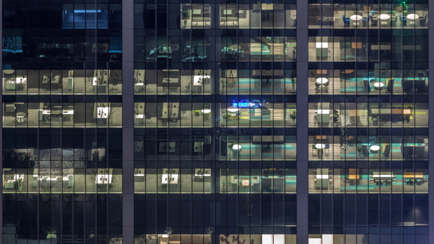 Office building exterior during late evening with interior lights on and people working inside night timelapse. Aerial close up view from above with many illuminated windows. Pan down | Shutterstock HD Video #1036030166