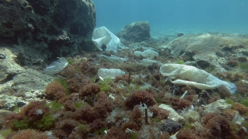 Slow motion. Plastic pollution of the ocean bottom, Tropical fishes swims over the bottom covered with a lot of plastic garbage. Plastic bottles, bags and dishes on the seabed in Mediterranean Sea.