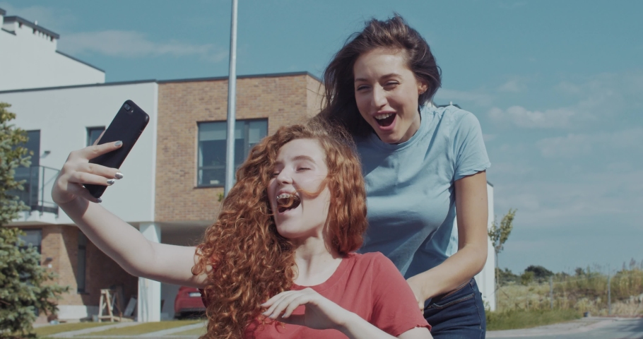 Two happy girlfriends spending time outdoors on lovely sunny day. Pretty girl riding a disabled invalid ginger cutie taking selfies having fun activity in the street. | Shutterstock HD Video #1036040486