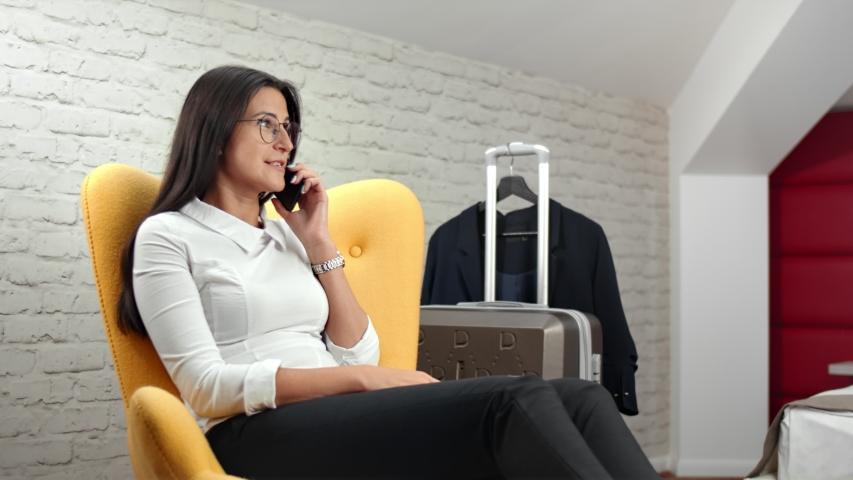 Smiling beautiful businesswoman talking using smartphone during business trip medium shot | Shutterstock HD Video #1036078106
