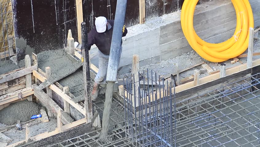 Worker at construction site unfinished construction for Poured concrete basement cost